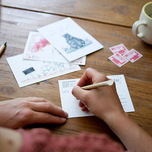 Frau schreibt Postkarte aus Samenpapier zu Hause.