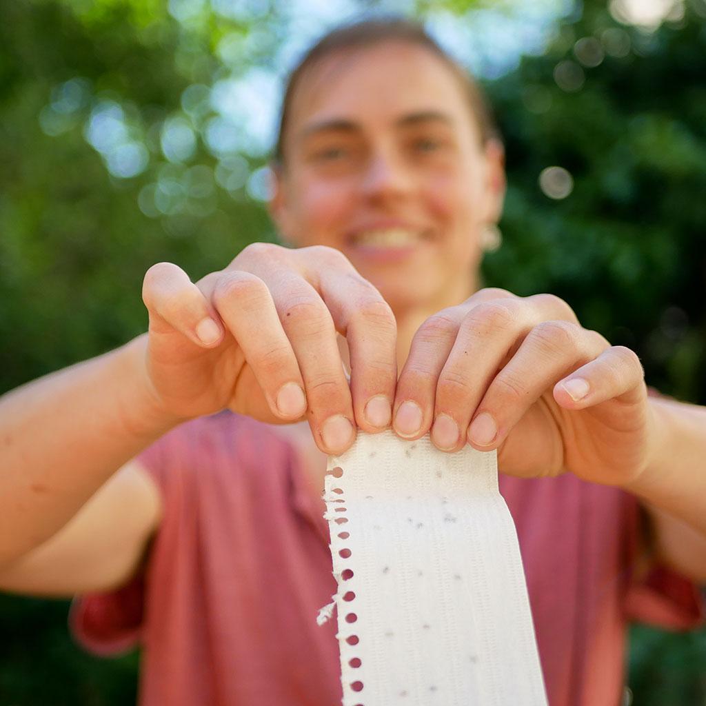 Frau zerreißt Kalenderblatt aus Samenpapier aus dem Wachsenden Kalender. Natur im Hintergrund.
