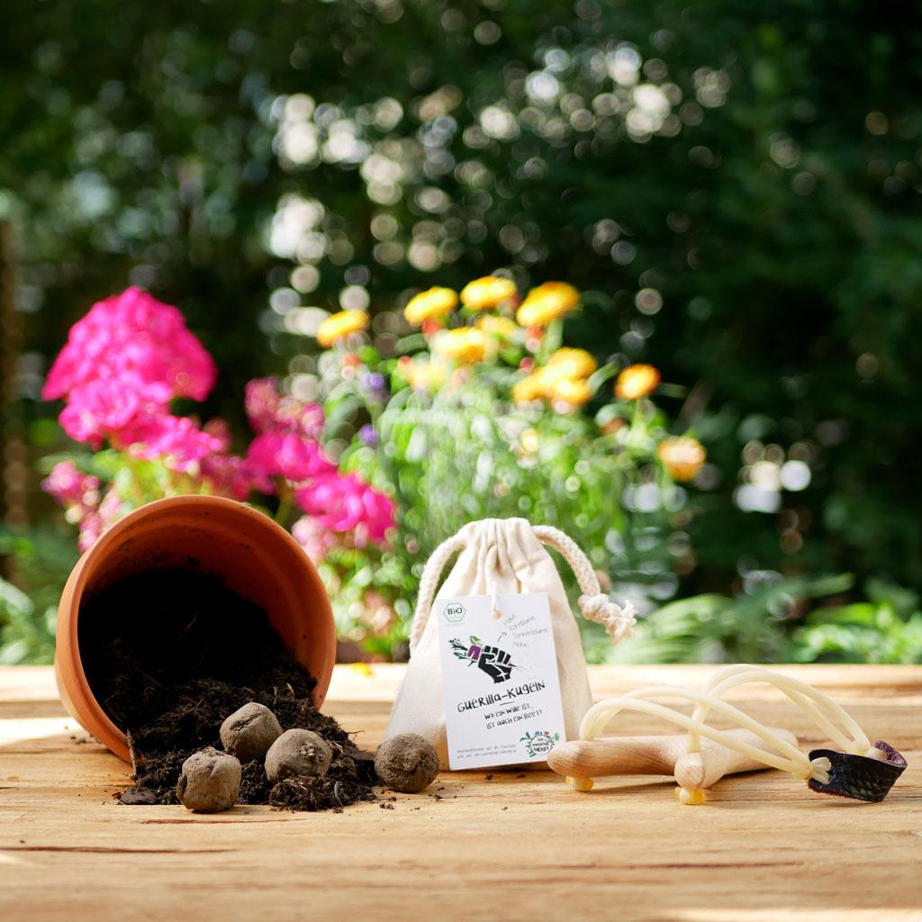 """Bio-Samenbomben """"Guerilla Kugeln"""" mit bienenfreundlichen Blumensamen im Leinensäckchen plastikfrei. Hintergrund Stadtgarten, Erde und Steinschleuder"""