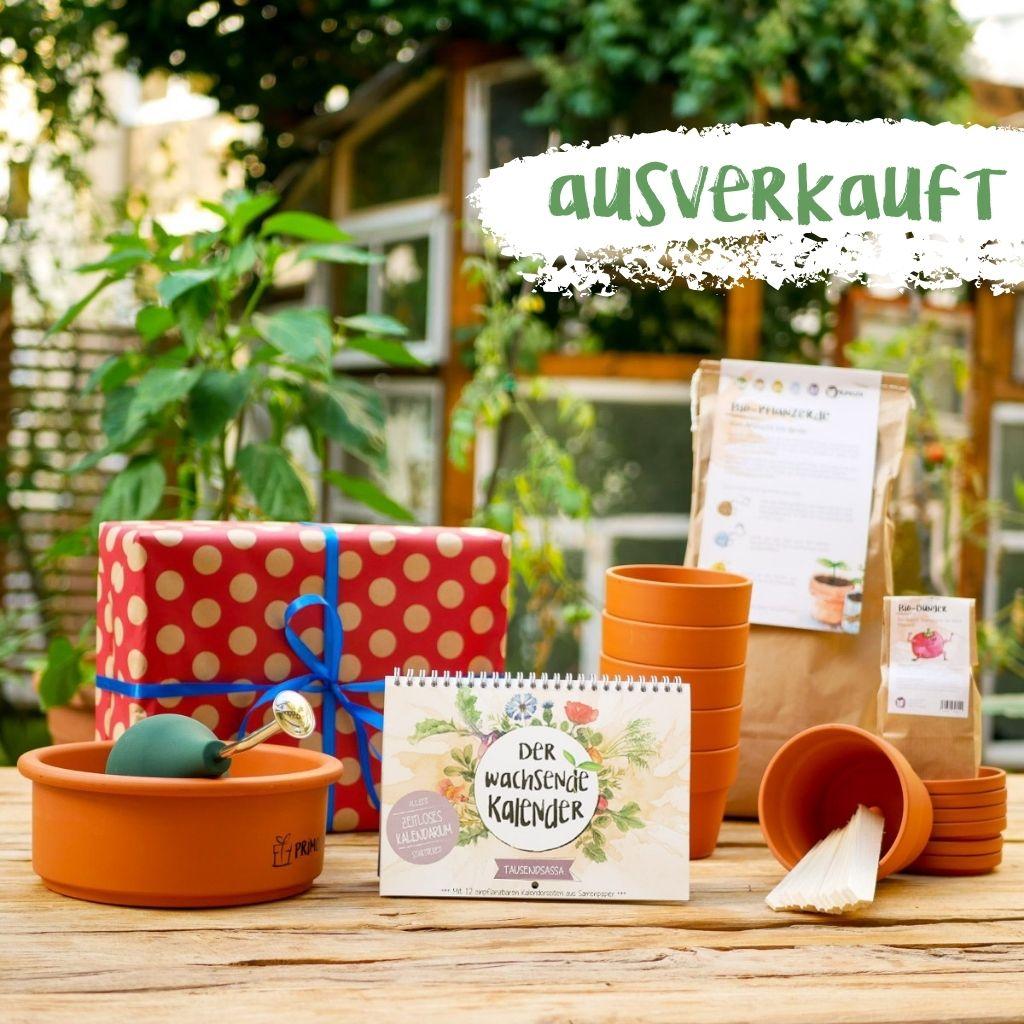 Geschenkset aus Einpflanzhilfen wie Tontöpfen, Bio-Erde und Dünger und einem Wachsenden Kalender Tausendsassa. Alles steht ausgestellt auf einem Holztisch im Garten.