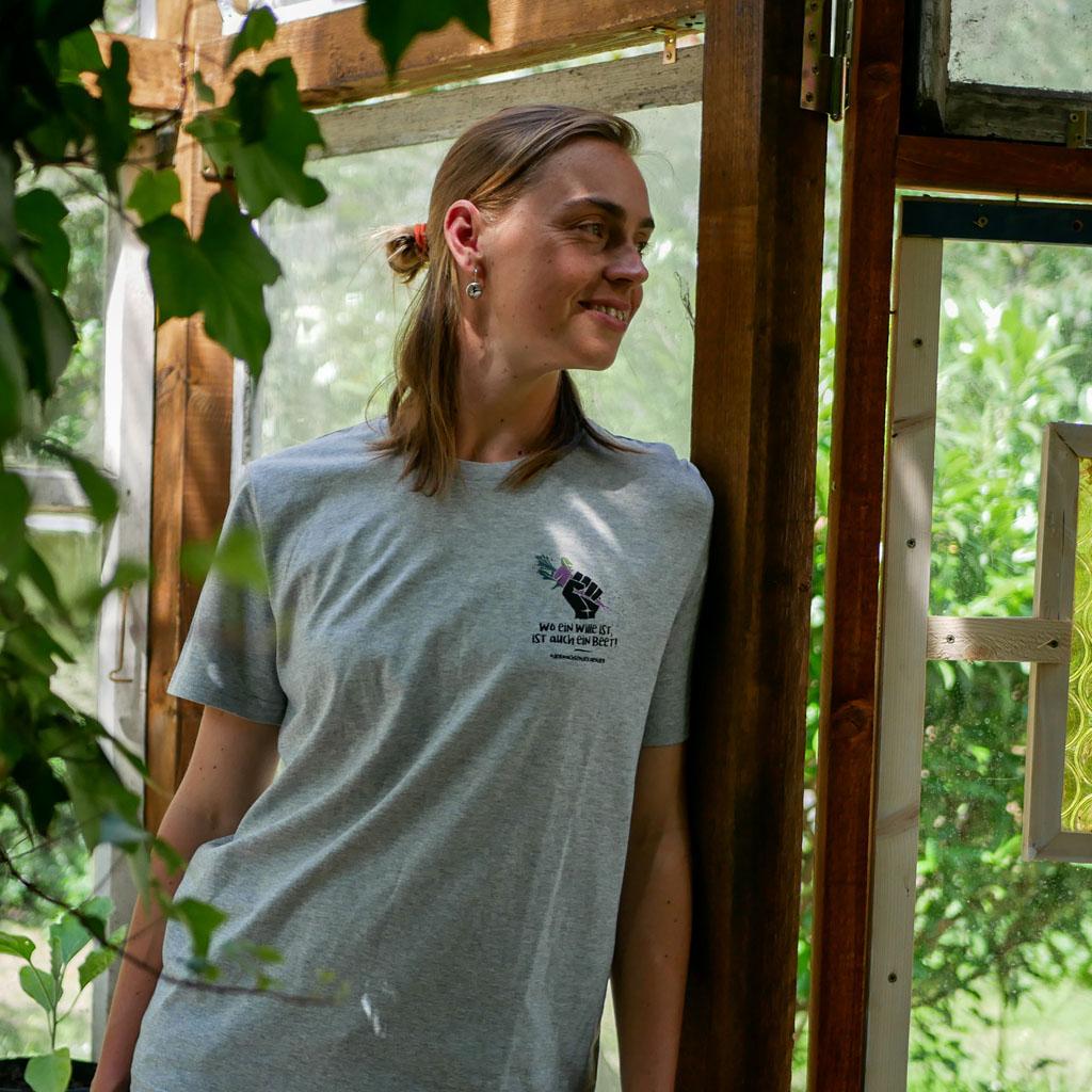 """Frau im Gewächshaus trägt graues T-Shirt mit Motiv """"Wo ein Wille ist, ist auch ein Beet""""."""
