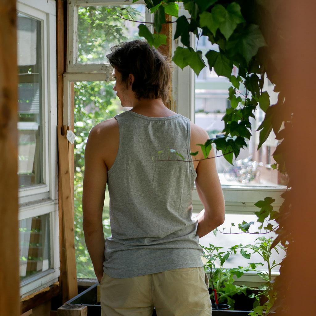 """Mann im Gewächshaus trägt graues Top mit Motiv """"Wo ein Wille ist, ist auch ein Beet""""."""