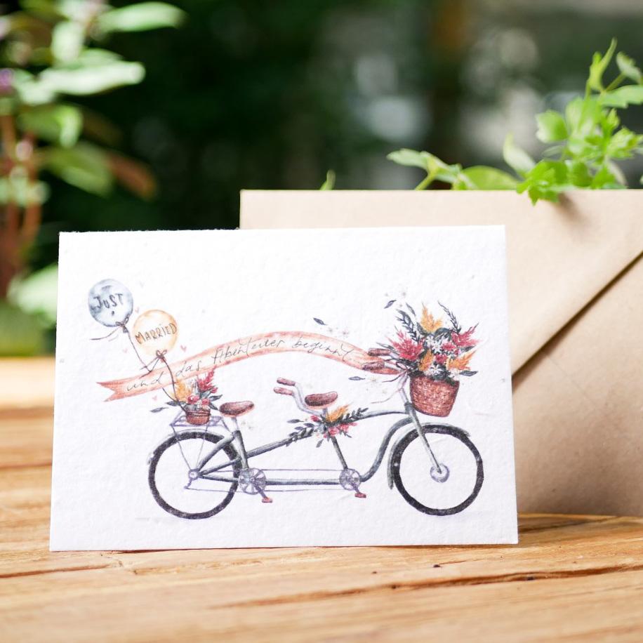 Einpflanzbare Klappkarte aus Samenpapier. Karte zur Hochzeit mit handgezeichnetem Motiv mit Tandem-Fahrrad. Mit Umschlag aus Graspapier