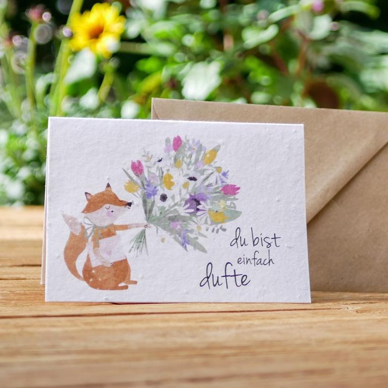 Einpflanzbare Klappkarte aus Samenpapier. Grußkarte mit handgezeichnetem Motiv mit Fuchs und Blumenstrauß. Mit Umschlag aus Graspapier
