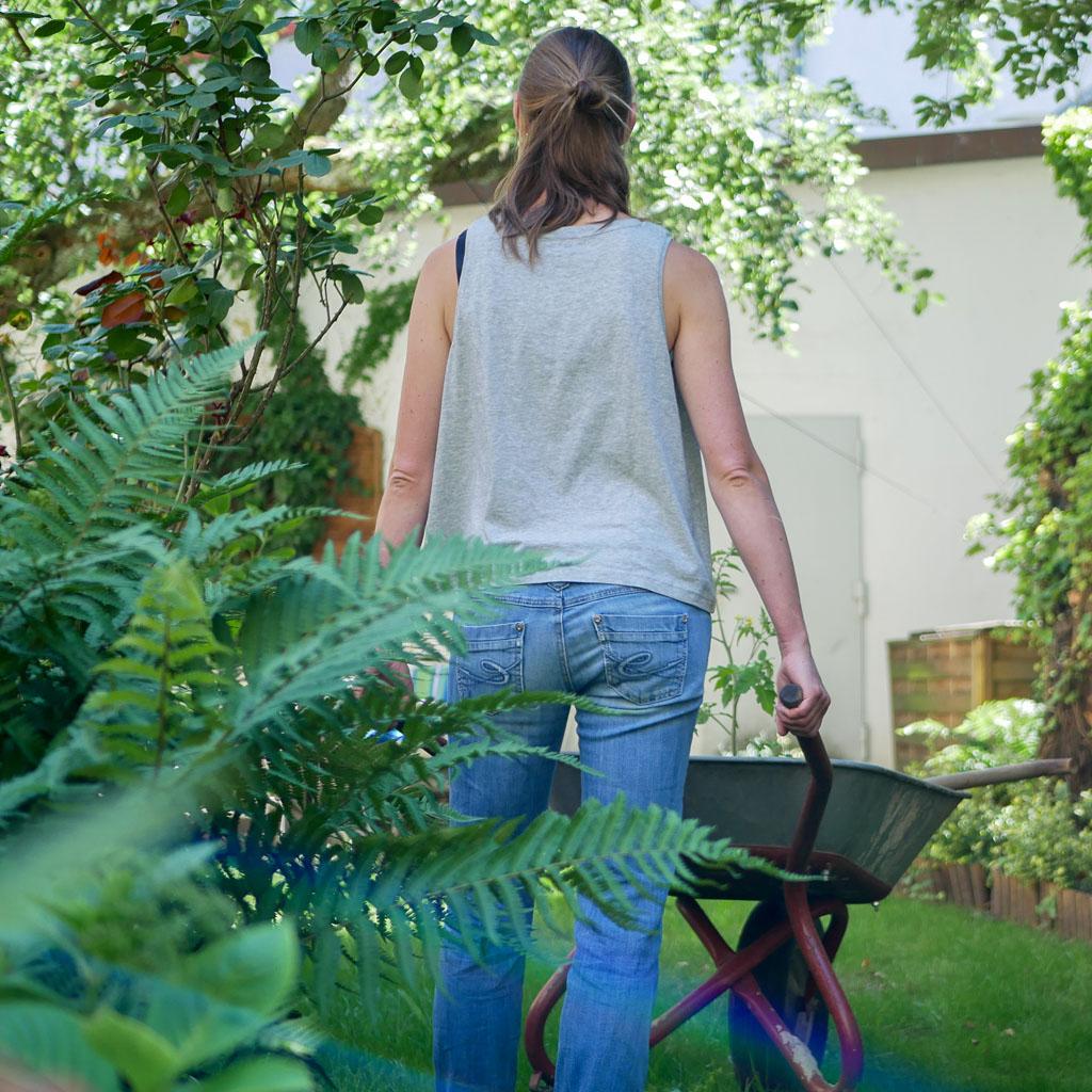 """Frau im Garten trägt graues Top mit Motiv """"Wo ein Wille ist, ist auch ein Beet""""."""