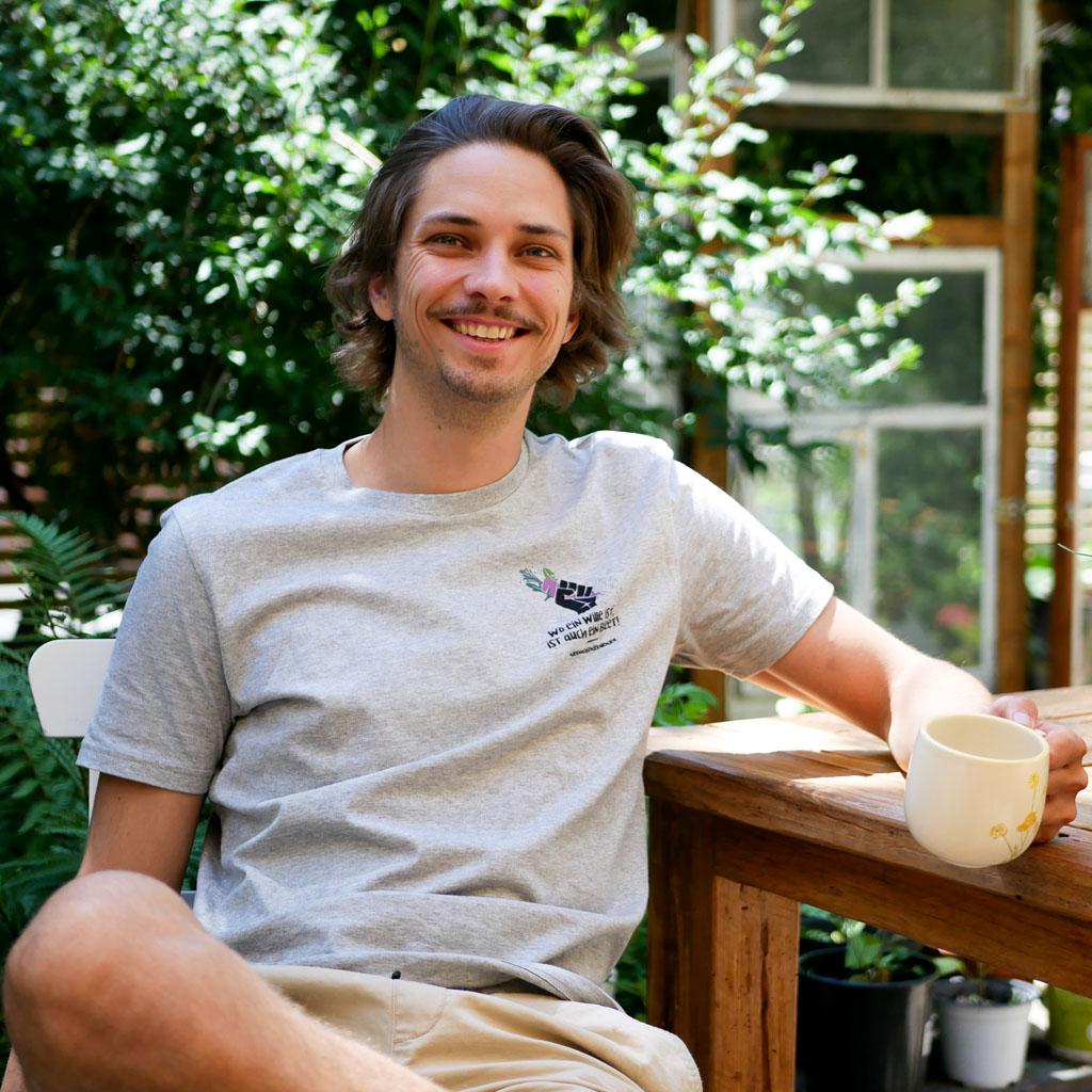 """Mann im Garten trägt graues T-Shirt mit Motiv """"Wo ein Wille ist, ist auch ein Beet""""."""