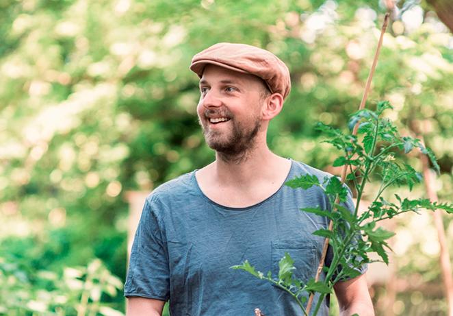 Gründer des nachhaligen Start Ups Primoza im Garten in der Stadt mit Pflanze