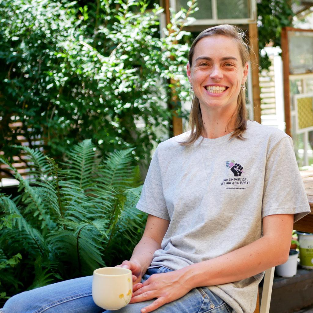 """Frau im Garten trägt graues T-Shirt mit Motiv """"Wo ein Wille ist, ist auch ein Beet""""."""