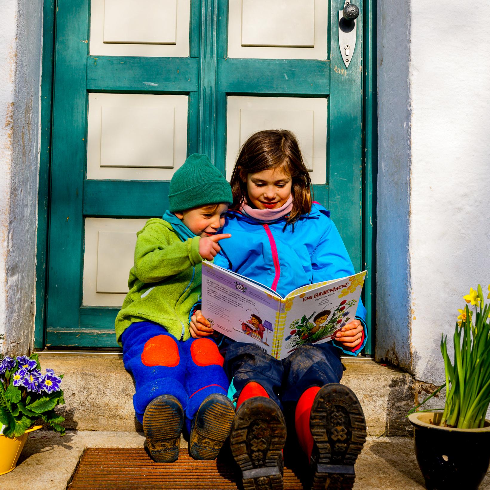 """Kinder lesen nachhaltiges und interaktives Kinderbuch """"Emi Brillenbiene"""" im Garten"""