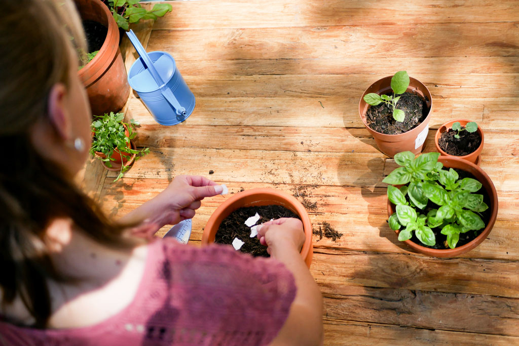 Frau pflanzt Grußkarten auf Samenpapier in einen Topf mit Erde. Im Hintergrund stehen Pflanzen und eine Gießkanne.