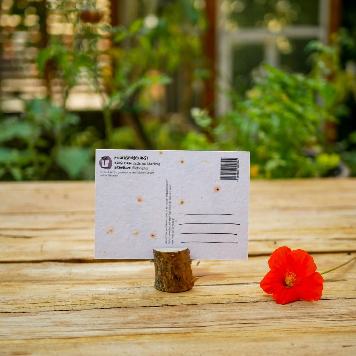 """Einpflanzbare Karte aus Samenpapier mit Blumenmotiv und Spruch """"Dance to your own beet"""" steht auf Holztisch in einem Stadtgarten."""