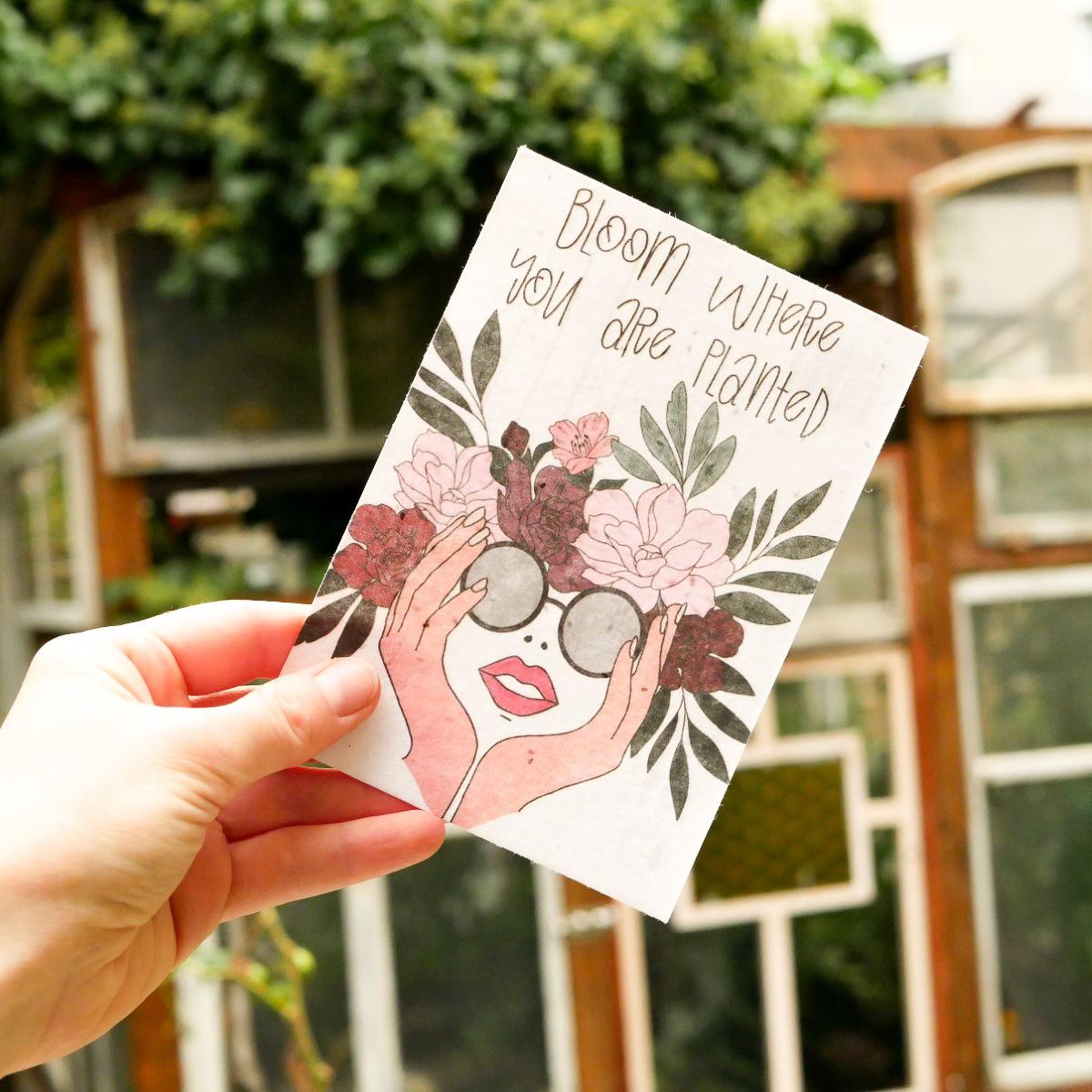 Einpflanzbare Postkarte aus Samenpapier mit Frau mit Sonnenbrille und Blumenkranz als Motiv.