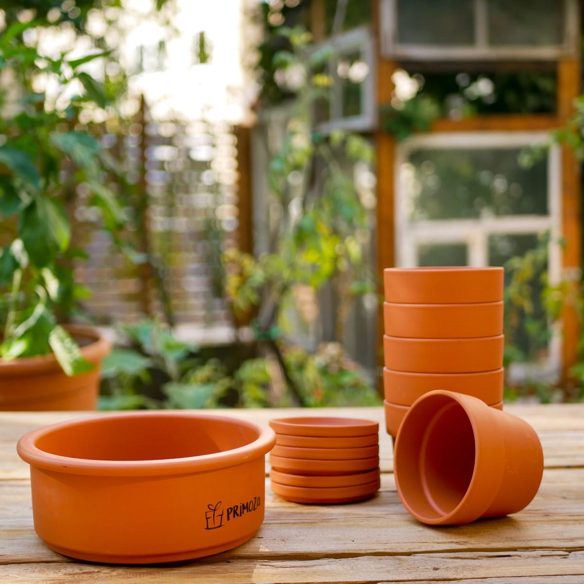 Ein Stapel kleiner Tontöpfe und eine Anzuchtschale aus Ton von primoza stehen auf einem Holztisch in einem Garten in der Stadt
