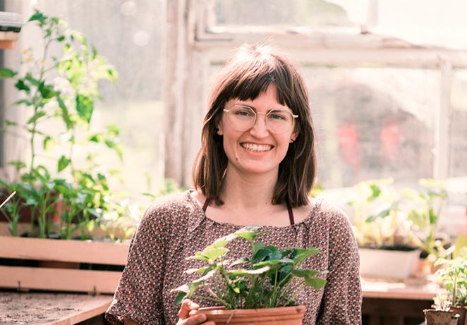 Gründerin des nachhaligen Start Ups Primoza im Gewächshaus in der Stadt mit Pflanze