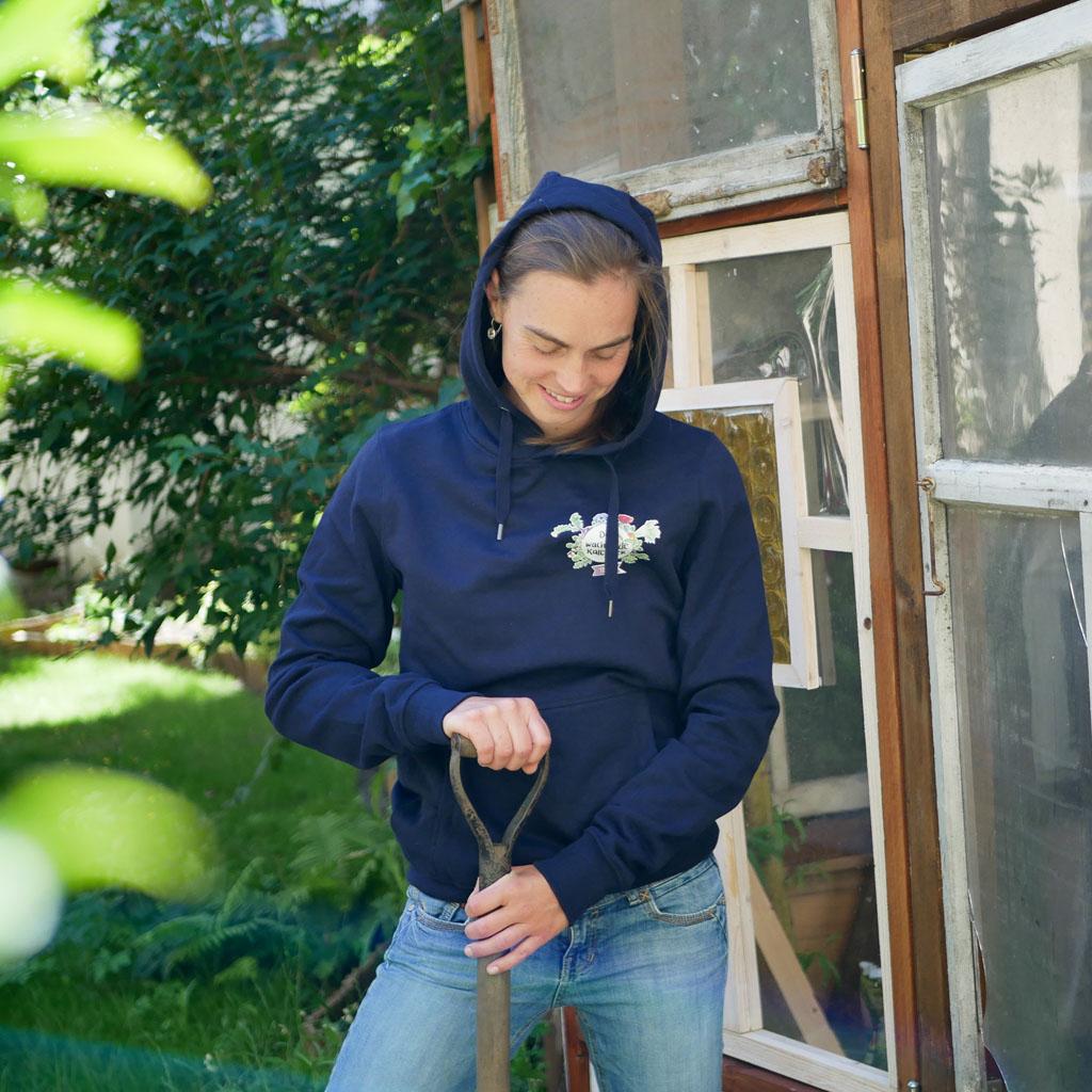 """Frau bei Gartenarbeit mit Gartenschaufel trägt dunkelblauen Pullover mit Motiv """"Der Wachsende Kalender""""."""