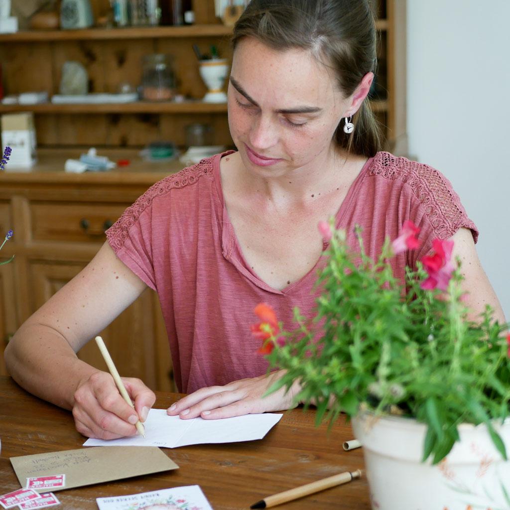 Frau schreibt zu Hause Grußkarte aus Samenpapier.