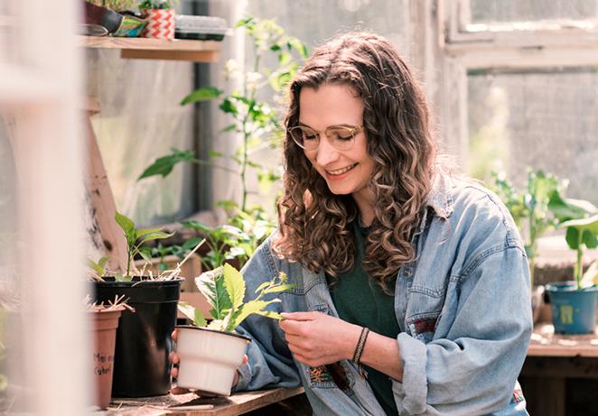 Teammitglied des nachhalitgen Start Ups Primoza im Gewächshaus in der Stadt mit Pflanze