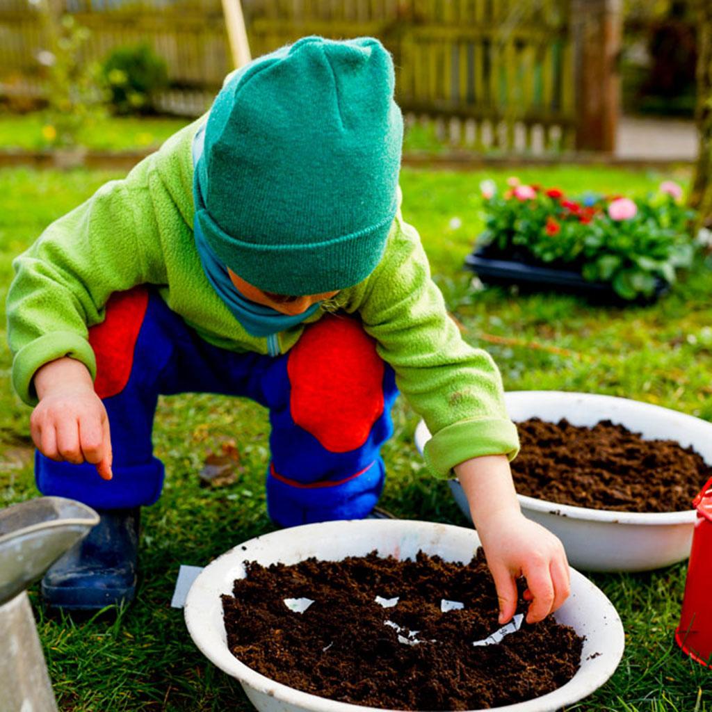 Kind pflanzt Samenpapier mit Samen bienenfreundlicher Blumen aus Kinderbuch Emi Brillenbiene in Erde