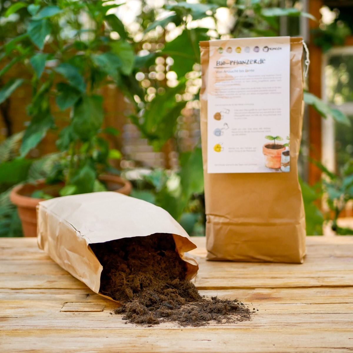 Zwei Säcke torffreie Bio-Erde stehen auf einem Holztisch. Sie sind in Papier verpackt und eine Packung ist geöffnet und leert sich auf einem Holztisch