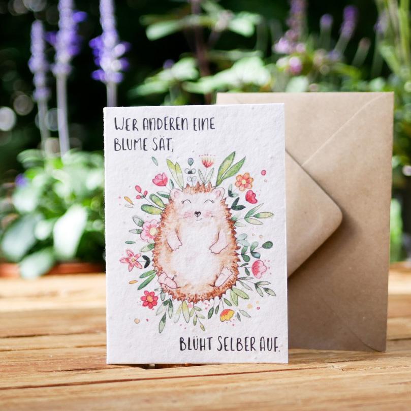 Einpflanzbare Klappkarte aus Samenpapier. Grußkarte mit handgezeichnetem Motiv mit Igel und Blumen. Mit Umschlag aus Graspapier