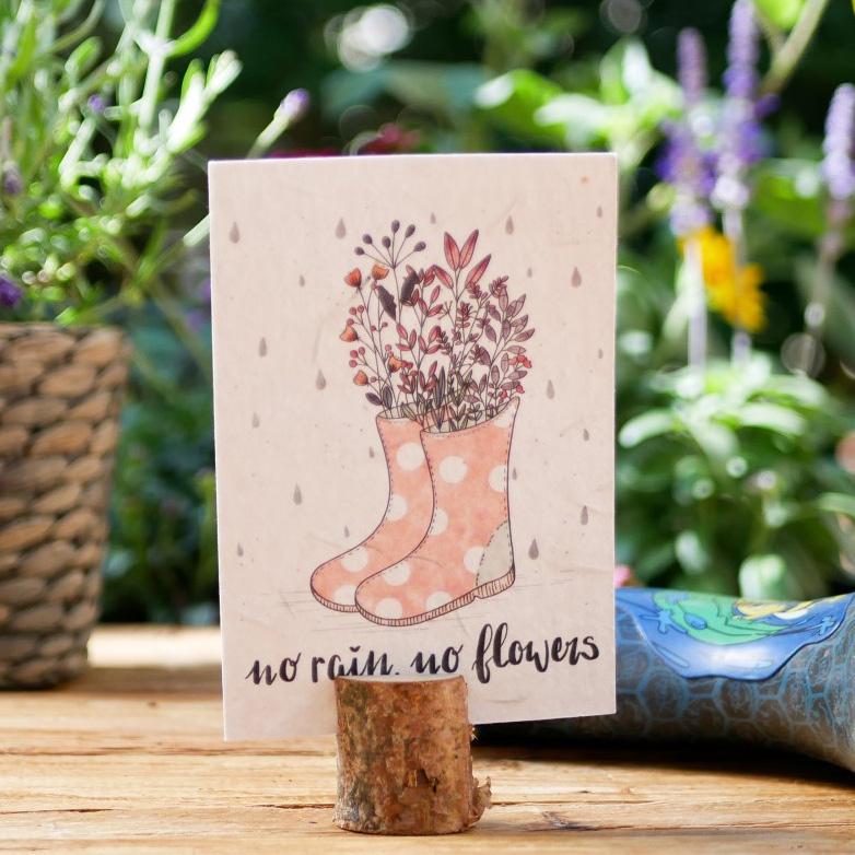 Einpflanzbare Postkarte aus Samenpapier. Karte zur Aufmunterung mit handgezeichnetem Motiv mit Regen und Gummistiefeln. Karte für den guten Zweck