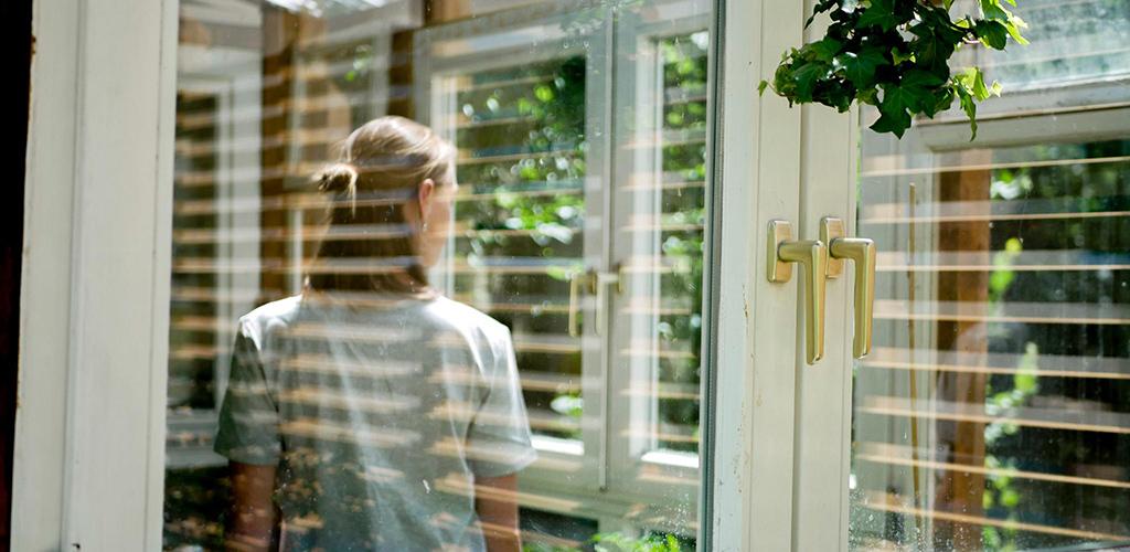 Frau trägt graues nachhaltiges T-Shirt und steht im Garten in der Stadt im Gewächshaus.