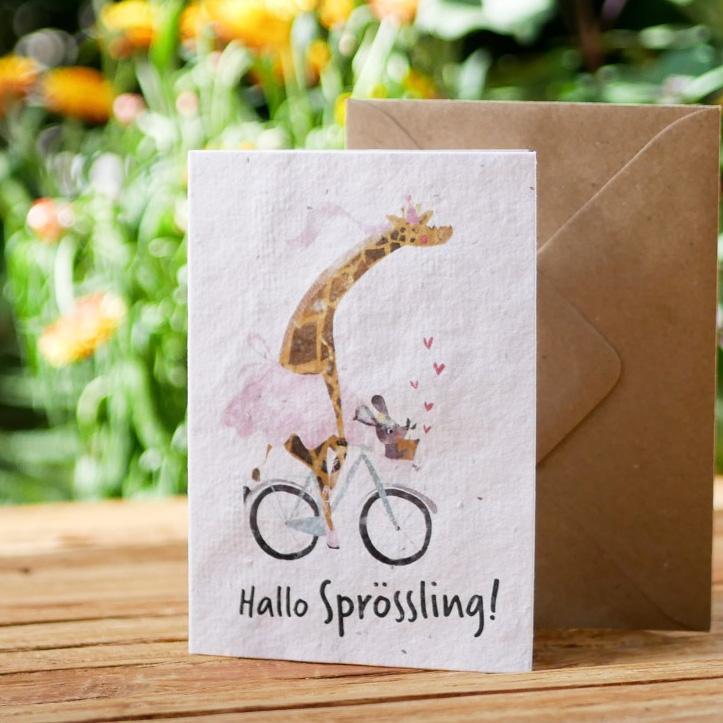 Einpflanzbare Klappkarte aus Samenpapier. Karte zur Geburt mit handgezeichnetem Motiv mit Giraffe, Maus und Fahrrad. Mit Umschlag aus Graspapier