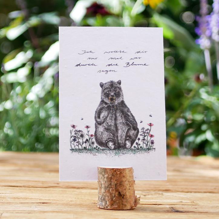 Einpflanzbare Postkarte aus Samenpapier. Grußkarte mit handgezeichnetem Motiv mit Bär und Blumenwiese. Karte für den guten Zweck.