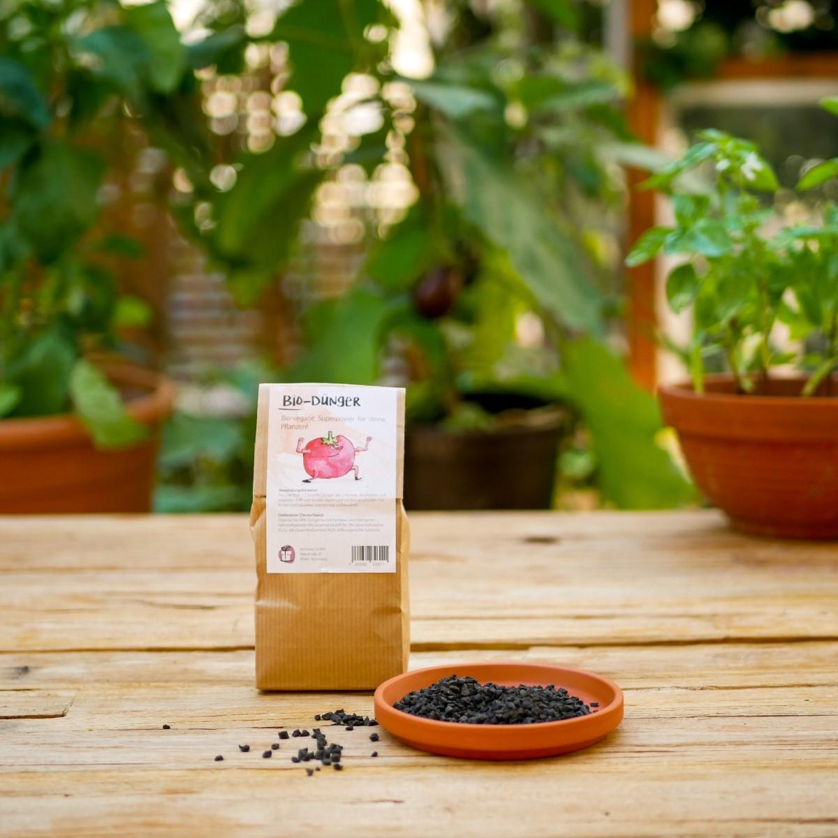 Bio-veganer Dünger in Papierverpackung steht auf einem Holztisch in einem Garten in der Stadt